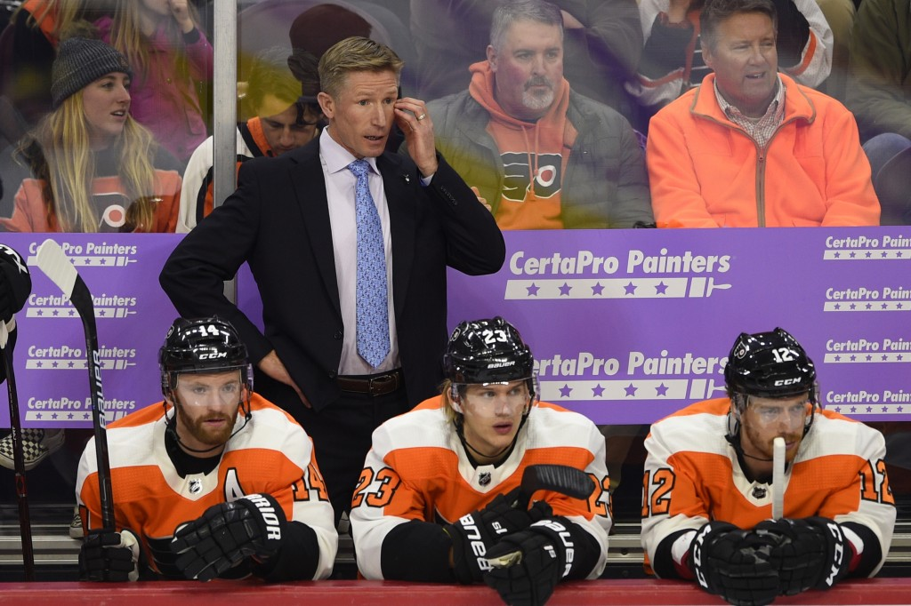 FILE - In this Nov. 27, 2018, file photo, Philadelphia Flyers head coach Dave Hakstol watches from the bench during an NHL hockey game against the Ott...