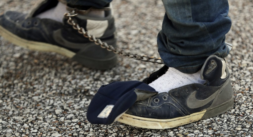 In this Nov. 16, 2018, photo, the shoelaces of an immigrant who entered the United States illegally is removed before boarding a deportation flight to...