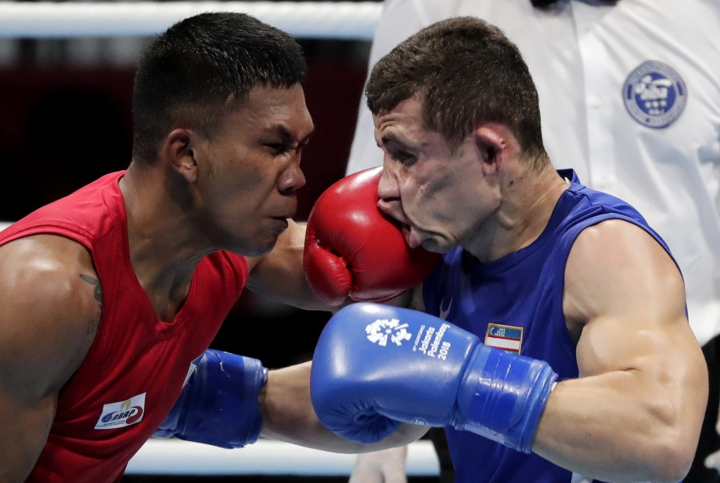Phillippines' Eumir Felix Marcial, red, and Uzbekistan's Israil Madrimov fight in their men's middleweight boxing semifinal at the 18th Asian Games in...