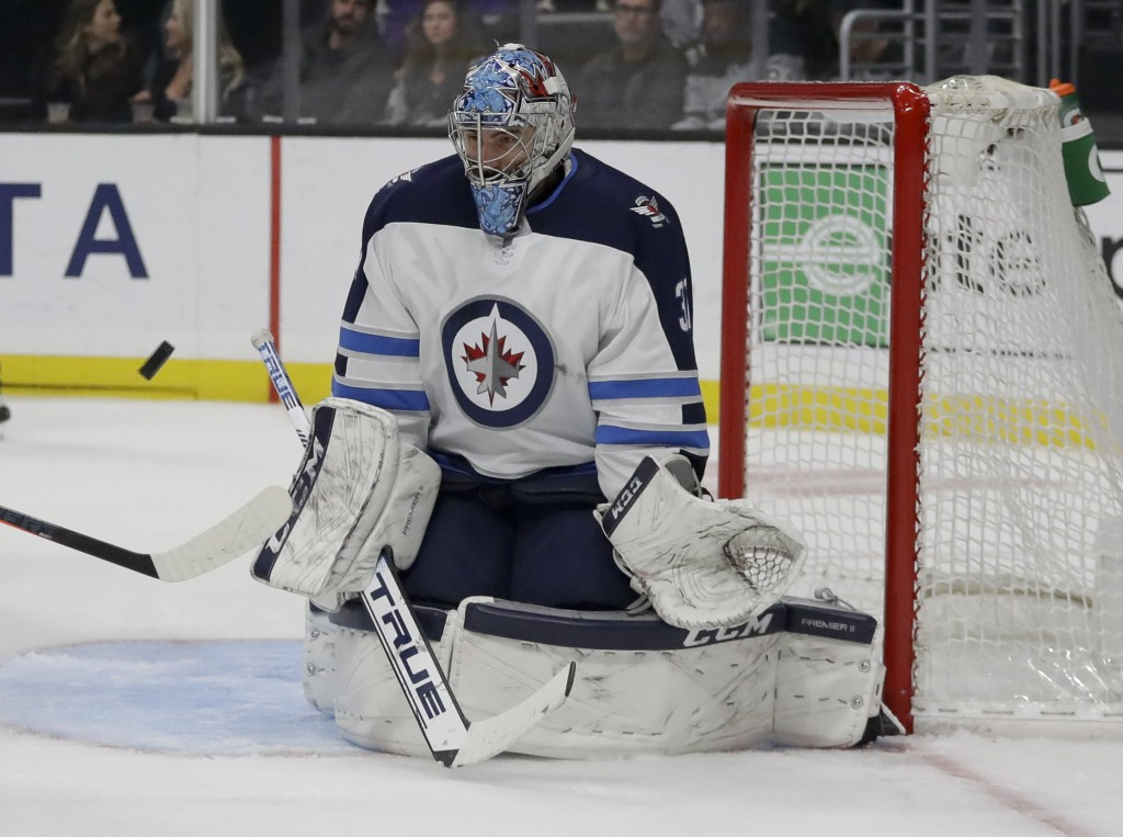 Winnipeg Jets goaltender Connor Hellebuyck blocks a shot during the second period of an NHL hockey game against the Los Angeles Kings in Los Angeles,