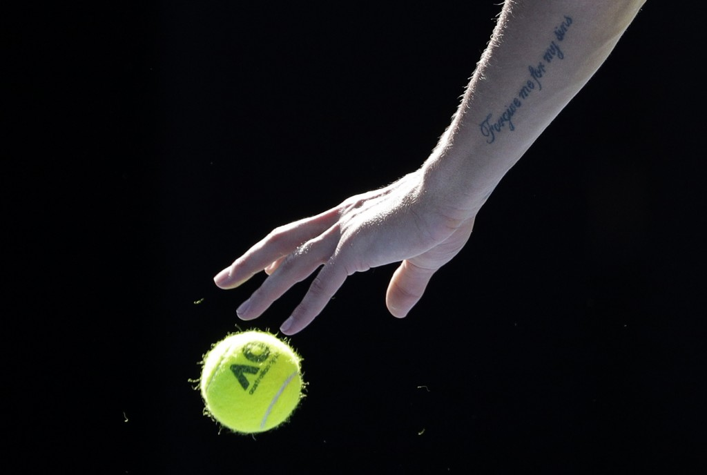 Hungary's Marton Fucsovics prepares to serve to Switzerland's Roger Federer during their fourth round match at the Australian Open tennis championship...