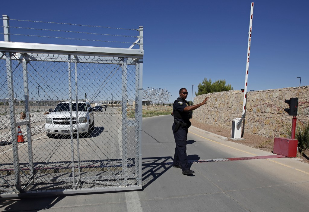FILE - In this June 21, 2018, file photo, an agent with the Department of Homeland Security controls access to a holding facility for immigrant childr