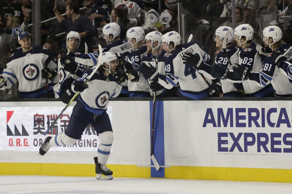Winnipeg Jets left wing Mathieu Perreault celebrates after scoring during the second period of an NHL hockey game against the Los Angeles Kings in Los
