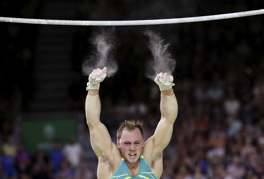 In this April 5, 2018 photo, Australia's Mitchell Morgans falls of the high bar as he competes at the men's artistic gymnastics competition at Coomera...