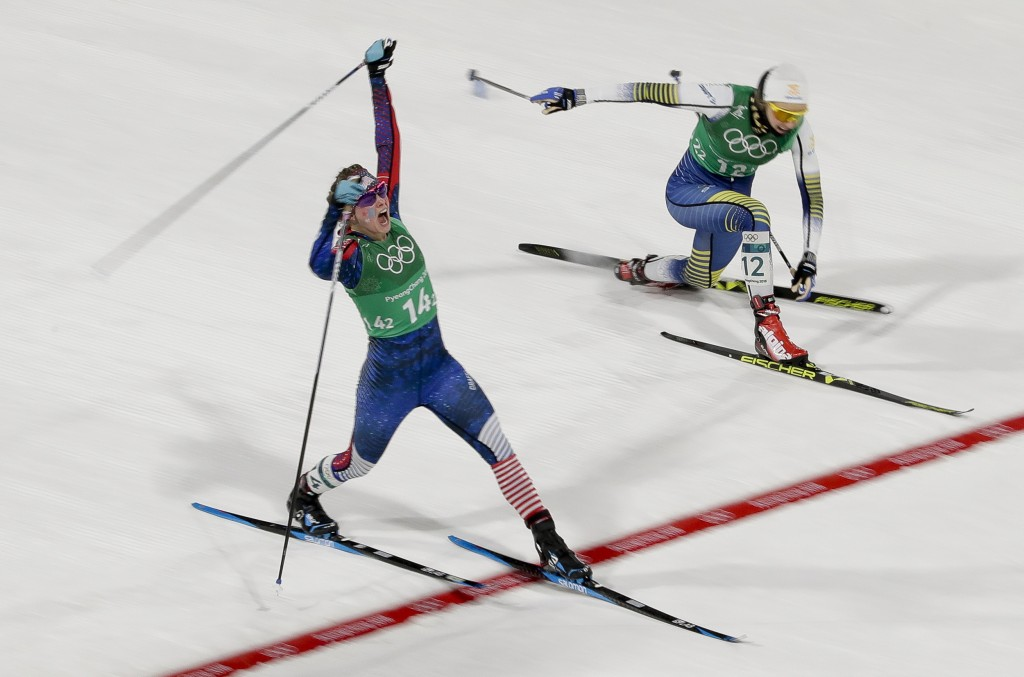 Jessica Diggins, left, of the United States, celebrates after winning the gold medal past Stina Nilsson, of Sweden, in the during women's team sprint