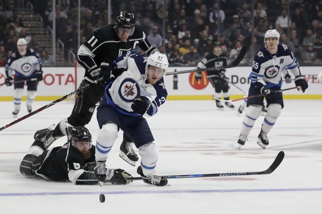 Winnipeg Jets left wing Nikolaj Ehlers (27) hits the puck away from Los Angeles Kings defenseman Jake Muzzin, bottom, and center Anze Kopitar during t