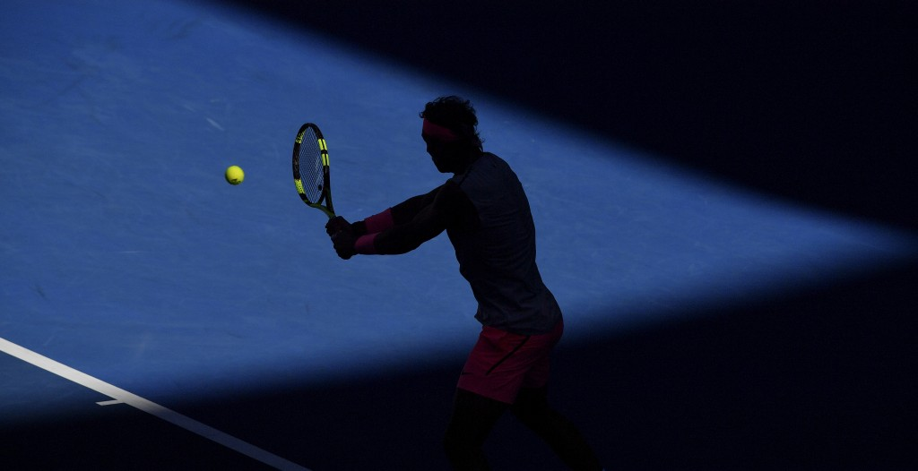 Spain's Rafael Nadal is silhouetted as he makes a backhand to Argentina's Leonardo Mayer during their second round match at the Australian Open tennis...