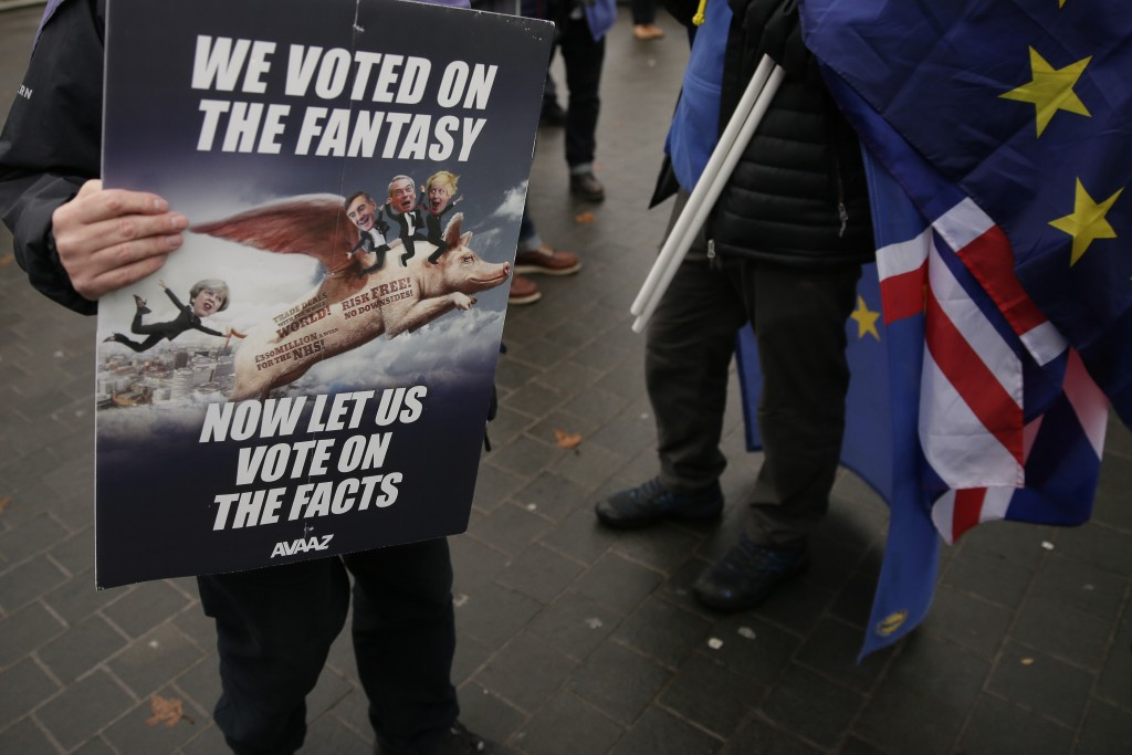 An anti-Brexit demonstrator holds a placard outside the houses of Parliament, in London, Wednesday Dec. 19, 2018. (AP Photo/Tim Ireland)