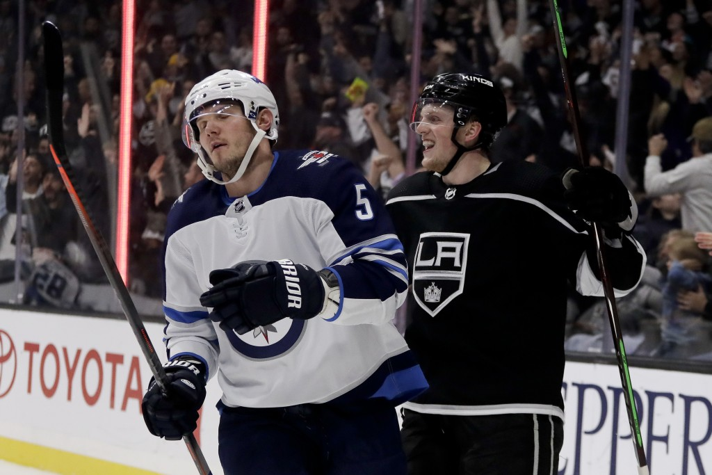 Los Angeles Kings left wing Austin Wagner, right, celebrates after scoring as Winnipeg Jets defenseman Dmitry Kulikov reacts during the second period