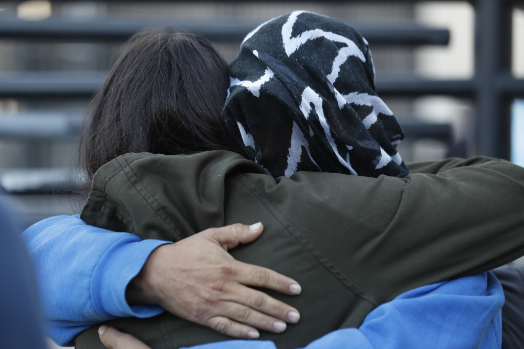A Honduran asylum seeker, his face covered with a blanket, embraces an activist before entering the U.S. at San Diego's Otay Mesa port of entry, as se