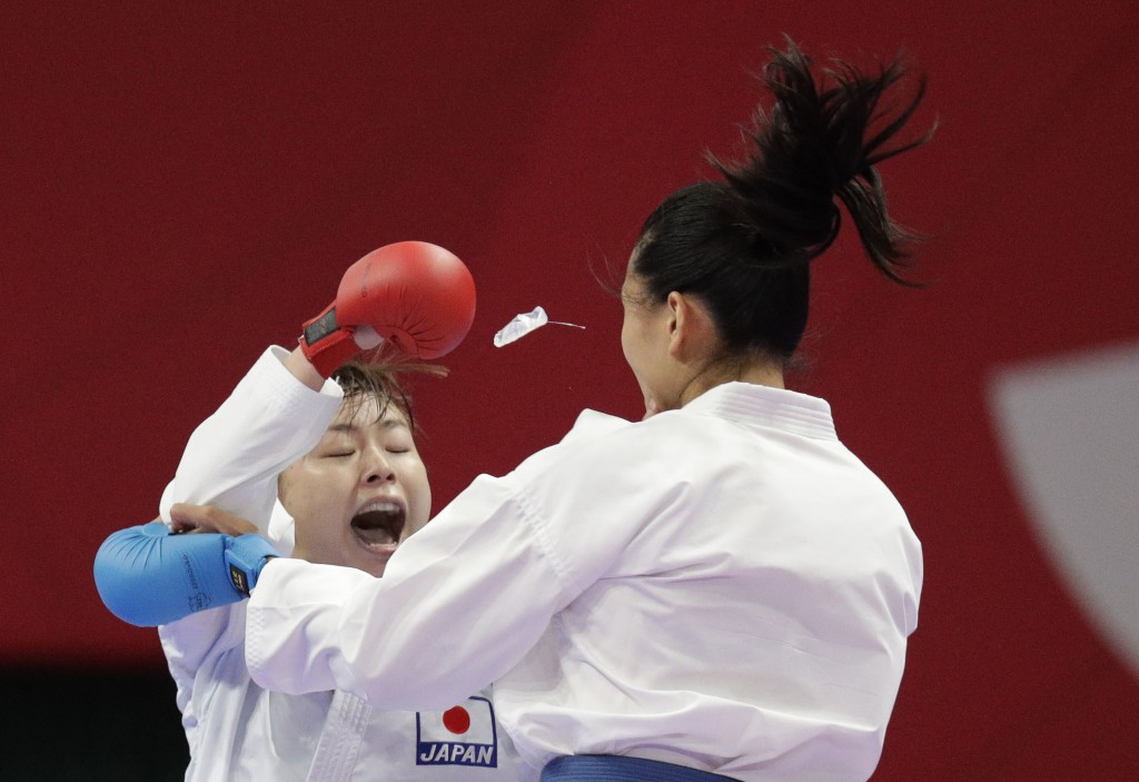 The mouthpiece of China's Mengmeng Gao, right, flies out during her fight with Japan's Ayumi Uekusa during their women's 68kg kumite karate at the 18t...