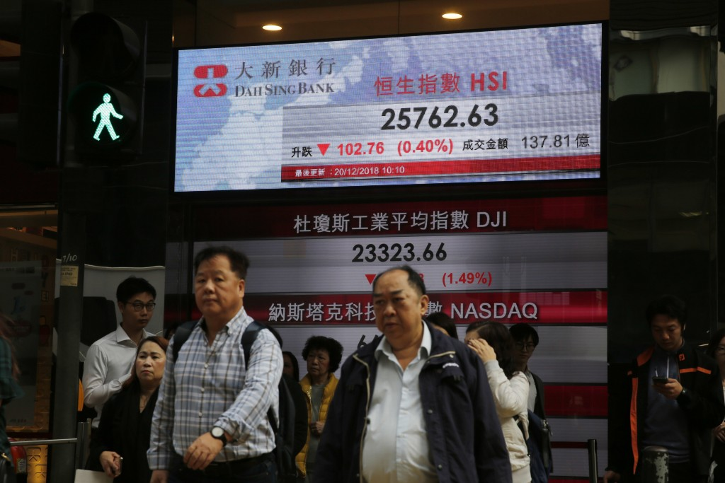 People walk across an electronic board showing Hong Kong share index outside a bank in Hong Kong, Thursday, Dec. 20, 2018. Asian stock markets sank Th...