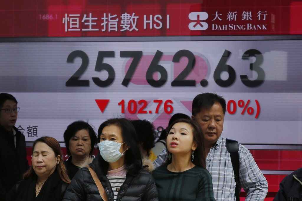 In this Thursday, Dec. 20, 2018, file photo, people stand in front of an electronic board showing Hong Kong share index outside a bank in Hong Kong. A...
