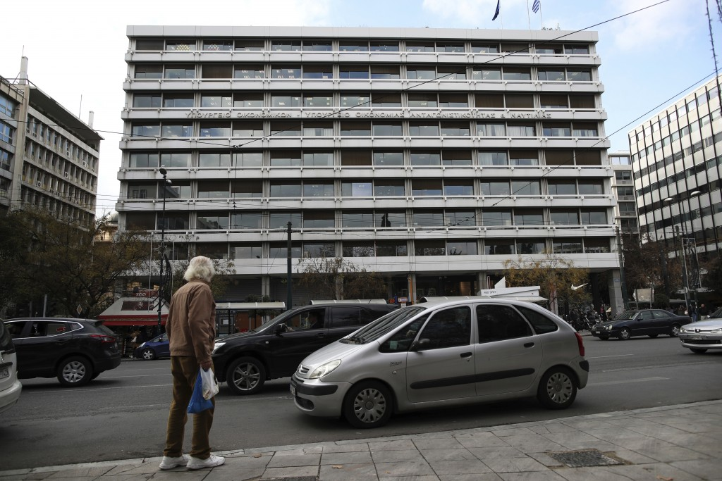 In this Thursday Dec. 20, 2018 photo, a man waits to cross the street as cars drive outside the building of the Greek Finance Ministry in central Athe