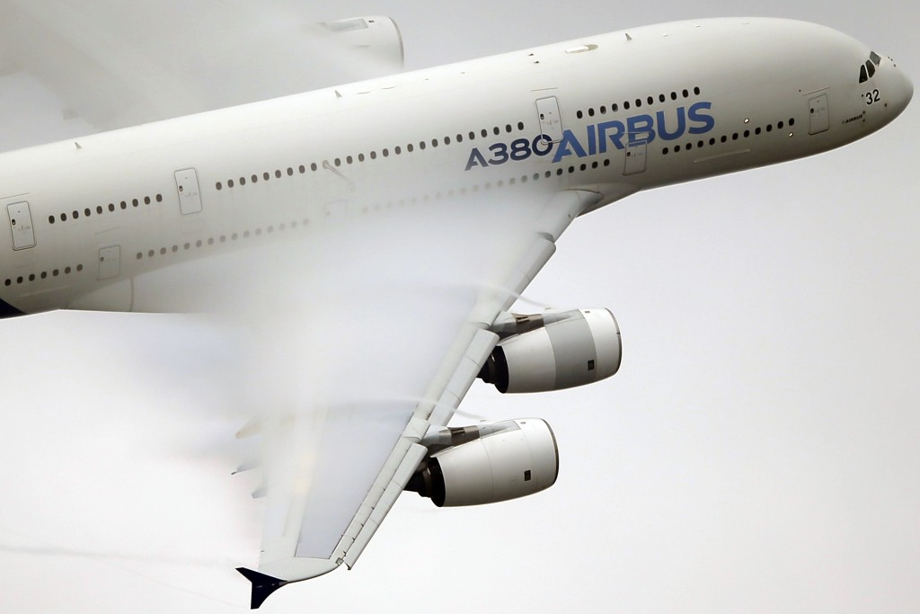 FILE - In this June 18 2015 file photo, vapor forms across the wings of an Airbus A380 as it performs a demonstration flight at the Paris Air Show, Le