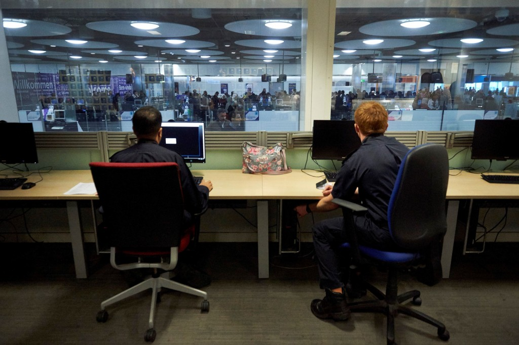 UK Border Force officers work in the watch room overlooking immigration control at Heathrow Airport's Terminal 5, in London, Wednesday Dec. 19, 2018. ...