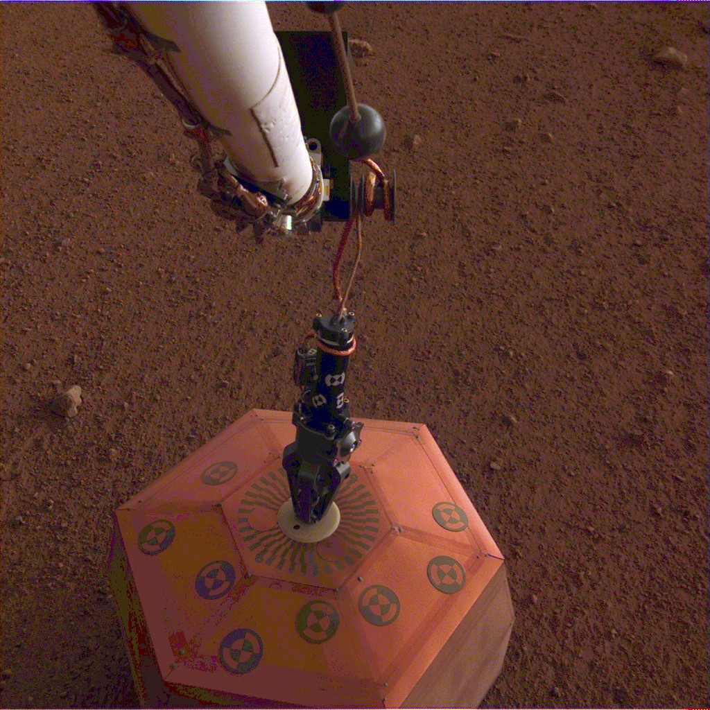 This photo provided by NASA Jet Propulsion Laboratory, shows the new Mars lander placing a quake monitor on the planet's dusty red surface.  The unpre