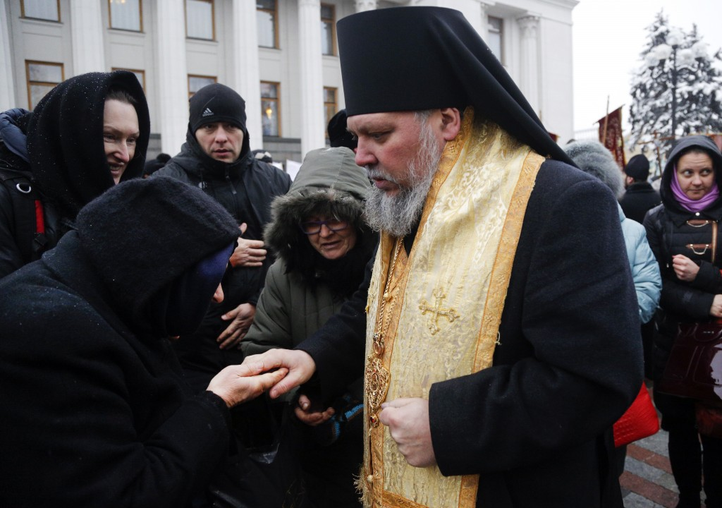 An Orthodox believer kisses the hand of a priest of the Ukrainian Orthodox Church of Moscow Patriarchy during a protest against the creation of a Ukra