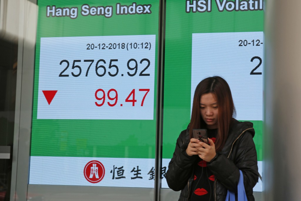 A woman uses her smartphone in front of an electronic board showing Hong Kong share index outside a bank in Hong Kong, Thursday, Dec. 20, 2018. Asian