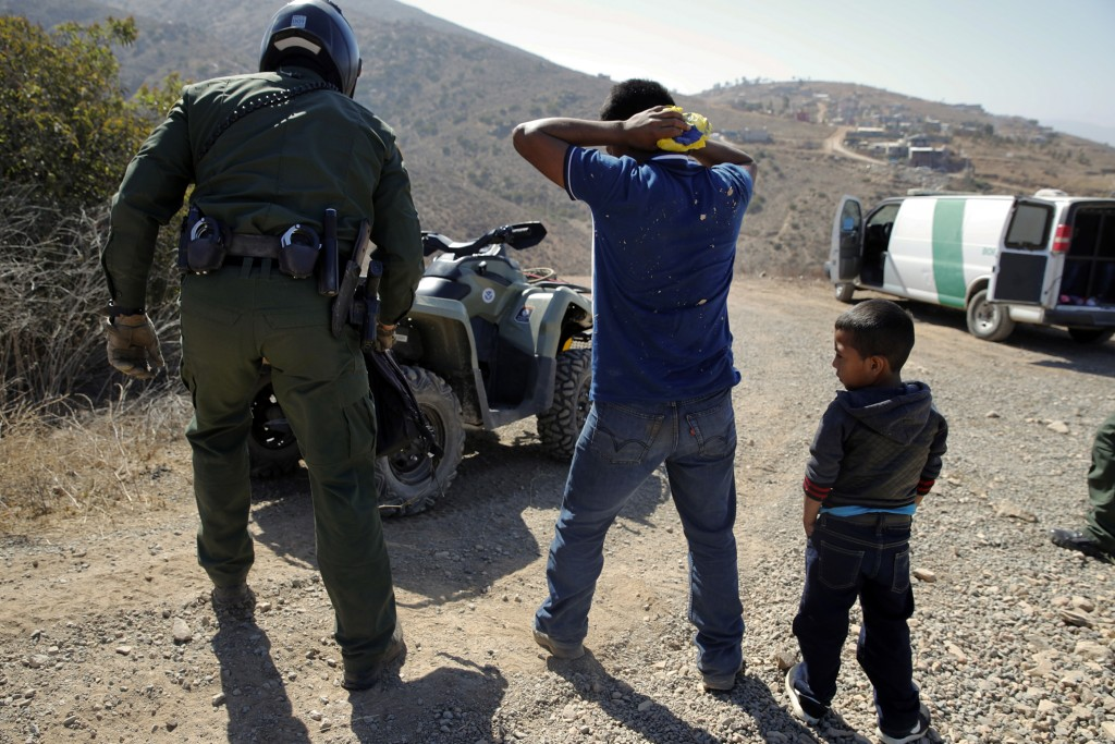 FILE - In this June 28, 2018, file photo, a Guatemalan father and son, who crossed the U.S.-Mexico border illegally, are apprehended by a U.S. Border