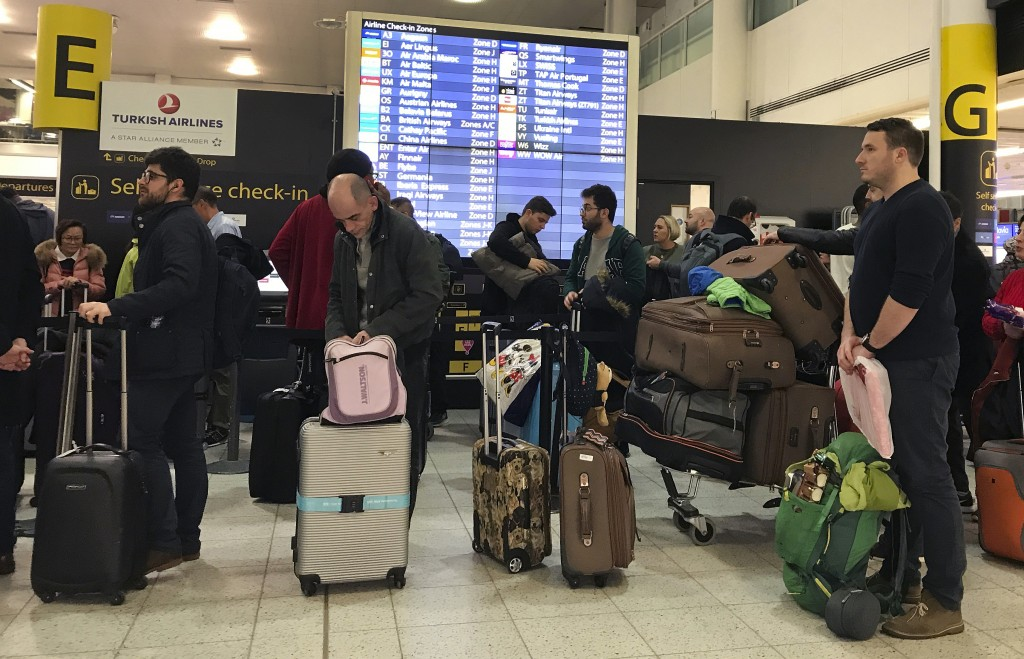 Passengers wait to check in at Gatwick Airport in England, Friday, Dec. 21, 2018. Flights resumed at London's Gatwick Airport on Friday morning after ...