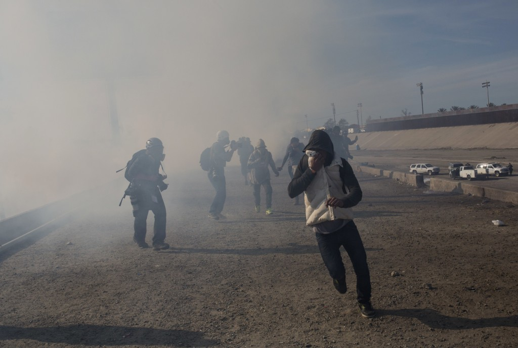 FILE - In this Nov. 25, 2018, file photo, migrants run from tear gas launched by U.S. agents, amid photojournalists covering the Mexico-U.S. border, a