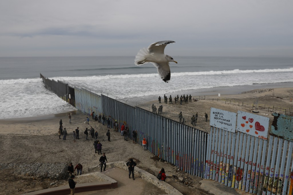 FILE - In this Dec. 10, 2018, file photo, people look on from the Mexican side, left, as U.S. Border Patrol agents on the other side of the U.S. borde