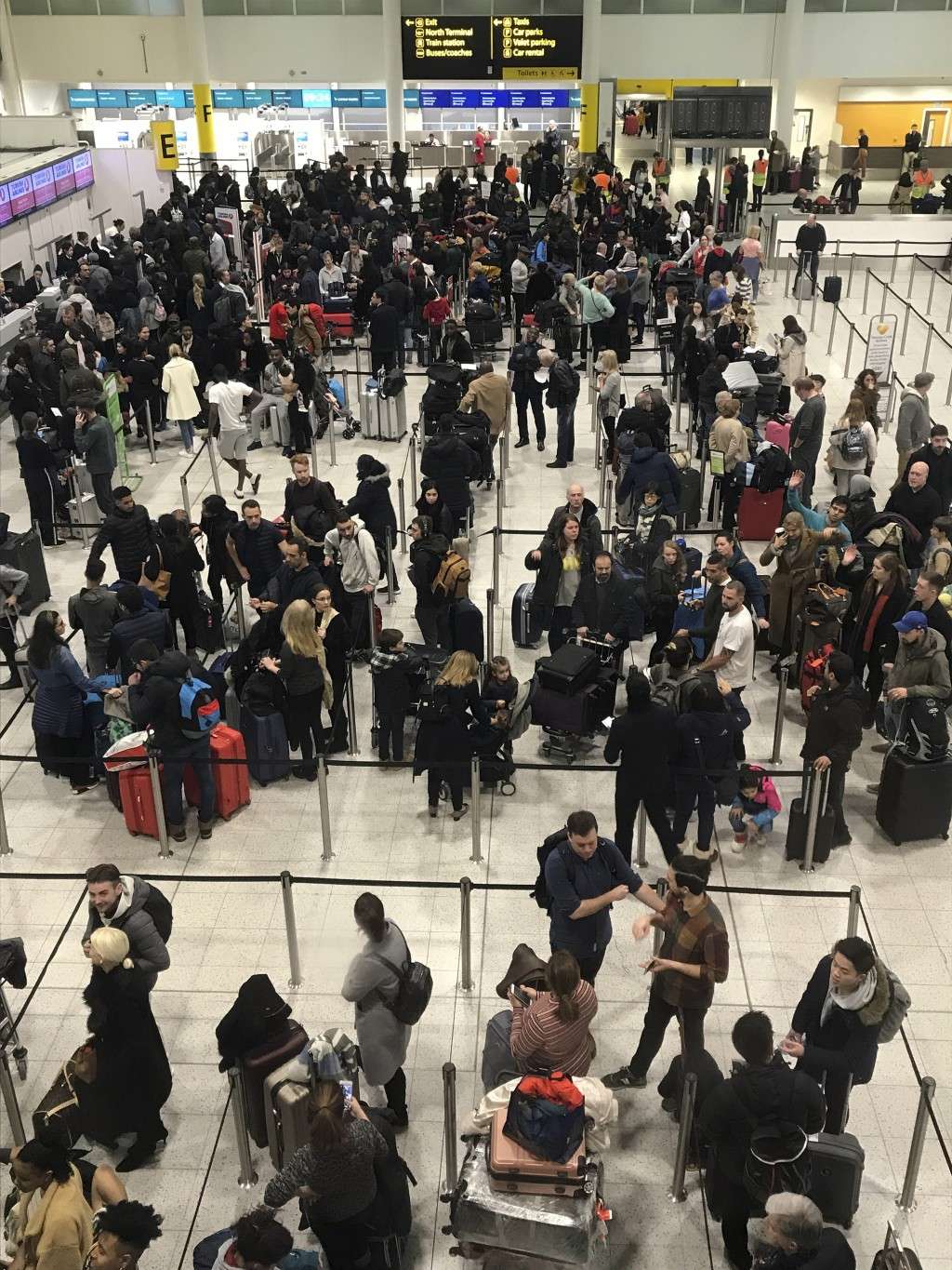Passengers wait to check in at Gatwick Airport in England, Friday, Dec. 21, 2018. Flights resumed at London's Gatwick Airport on Friday morning after