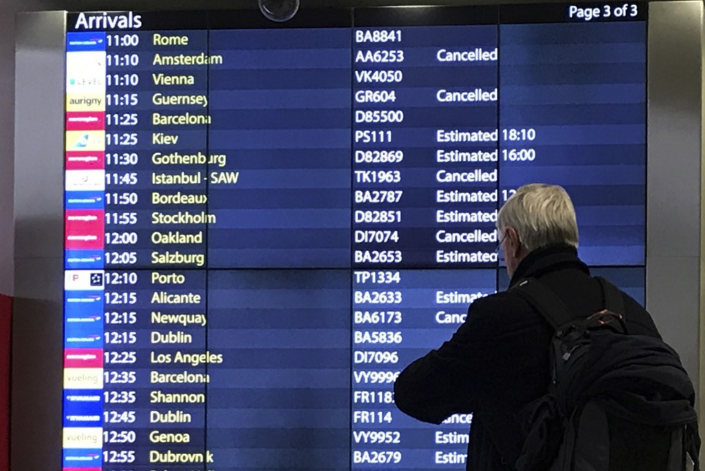 A passenger checks an arrivals board at Gatwick Airport in England, Friday, Dec. 21, 2018. Flights resumed at London's Gatwick Airport on Friday morni...
