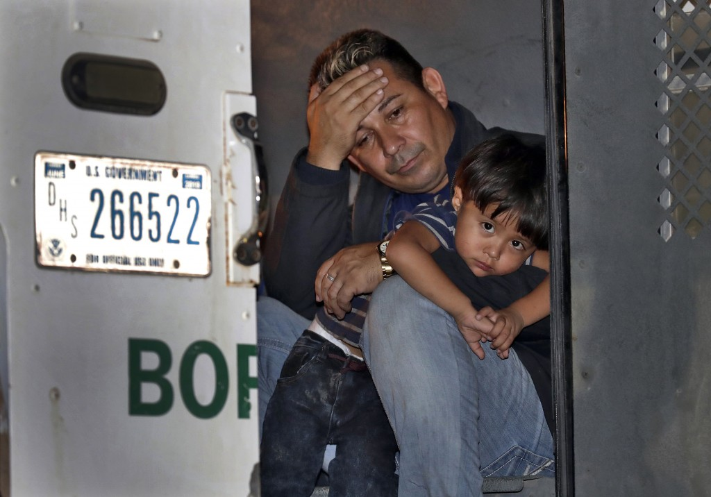 FILE - In this July 18, 2018, file photo, a father and his 3-year-old son are detained in the back of a U.S. Customs and Border Patrol vehicle on July