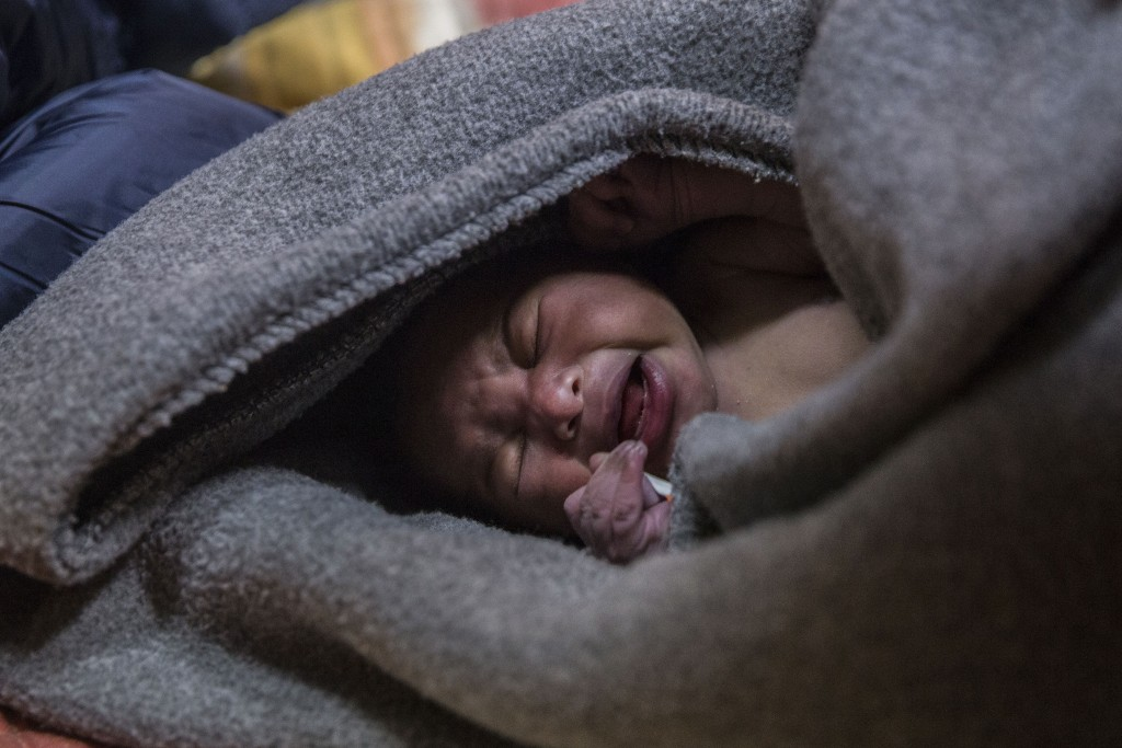 In this Friday, Dec. 21, 2018, photo, a baby cries on the deck of the Spanish NGO Proactiva Open Arms rescue vessel, after being rescued in the Centra...