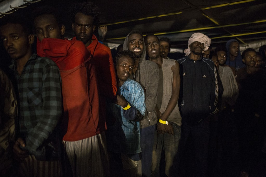 In this Friday, Dec. 21, 2018, photo, migrants stay at the deck of the Spanish NGO Proactiva Open Arms rescue vessel, after being rescued in the Centr