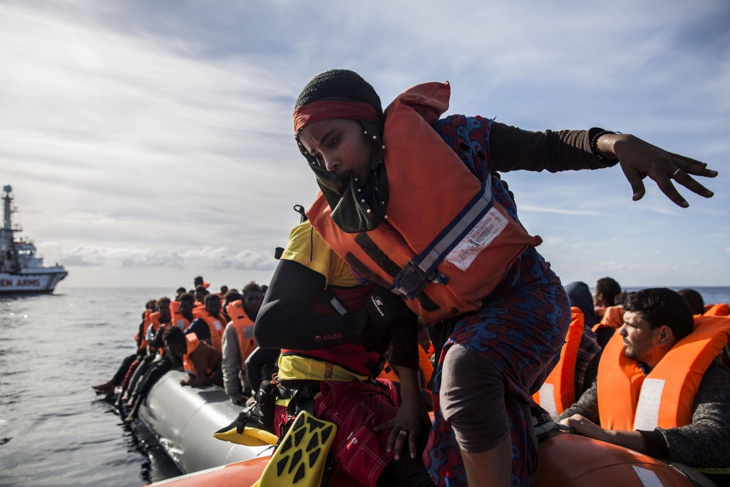 In this Friday, Dec. 21, 2018, photo, a woman is rescued by aid workers of Spanish NGO Proactiva Open Arms in the Central Mediterranean Sea at 45 mile