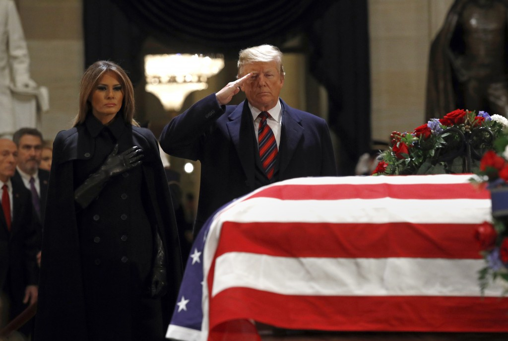 FILE -In this Dec. 3, 2018, file photo, President Donald Trump salutes alongside first lady Melania Trump in front of the flag-draped casket of former...