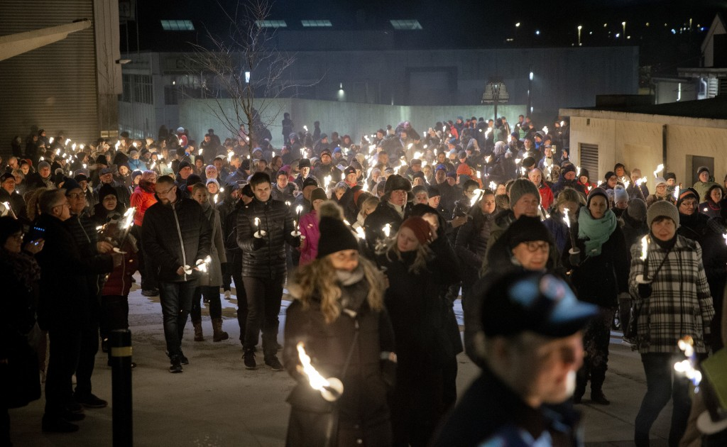 A group of people from Maren Ueland's hometown walk in a torch lit parade to honor Maren Ueland and Louisa Vesterager Jespersen from Denmark, who were