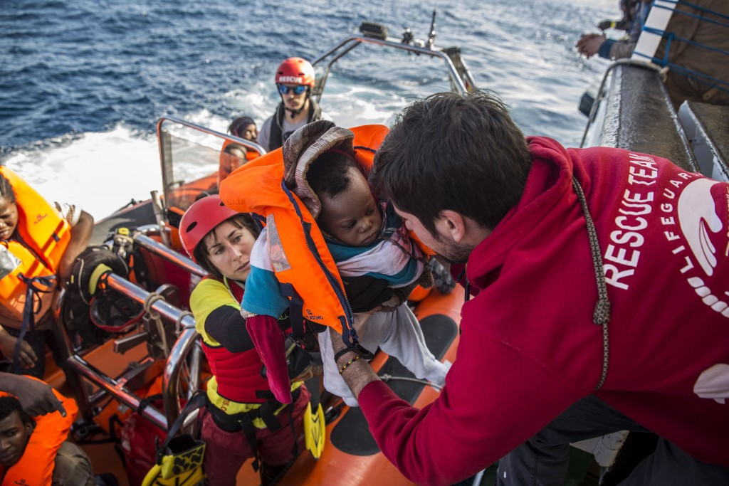 In this Friday, Dec. 21, 2018, photo, a baby is loaded into the rescue vessel of the Spanish NGO Proactiva Open Arms, after being rescued in the Centr