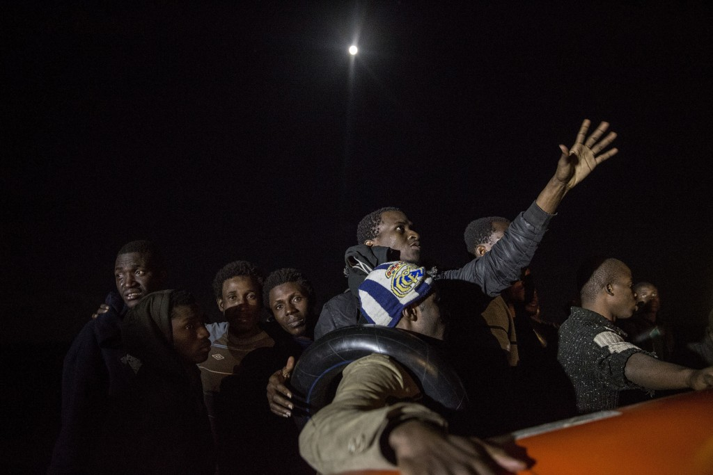 In this Friday, Dec. 21, 2018, photo, migrants react in a rubber dinghy after Proactiva Open Arms, a Spanish NGO, spotted and rescued them in the Cent...