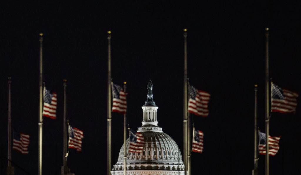 The U.S. Capitol Dome is seen beyond American Flags around the the base of the Washington Monument in Washington, early Saturday, Dec. 22, 2018. The A...