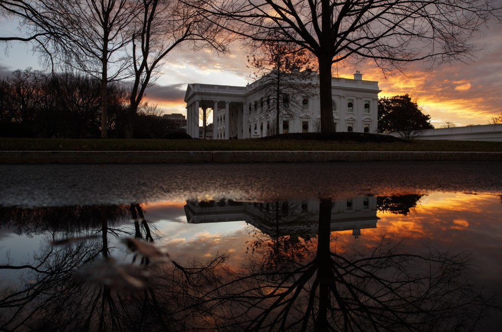 The sun rises behind the White House in Washington, Saturday, Dec. 22, 2018. Hundreds of thousands of federal workers faced a partial government shutd...