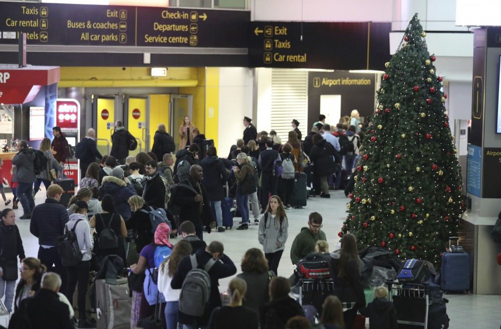 Passengers at Gatwick airport wait for their flights following the delays and cancellations brought on by drone sightings near the airfield, in London