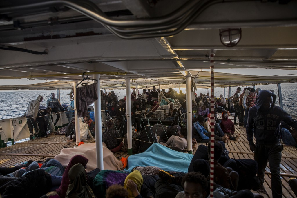 In this Friday, Dec. 21, 2018, photo, migrants stay at the deck of the Spanish NGO Proactiva Open Arms rescue vessel, after being rescued in the Centr...
