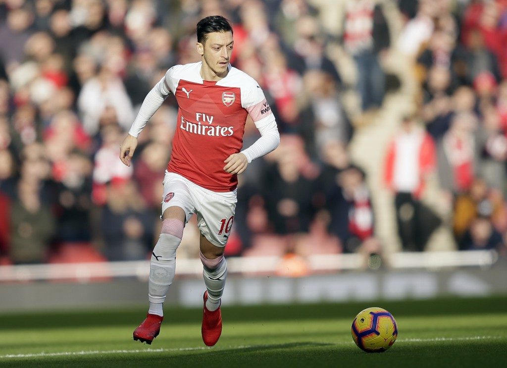 Arsenal's Mesut Ozil challenge for the ball during the English Premier League soccer match between Arsenal and Burnley at the Emirates Stadium in Lond...