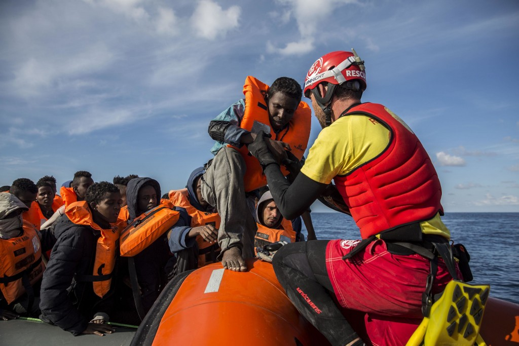 In this Friday, Dec. 21, 2018, photo, a man is helped by aid workers of Spanish NGO Proactiva Open Arms, after being rescued in the Central Mediterran