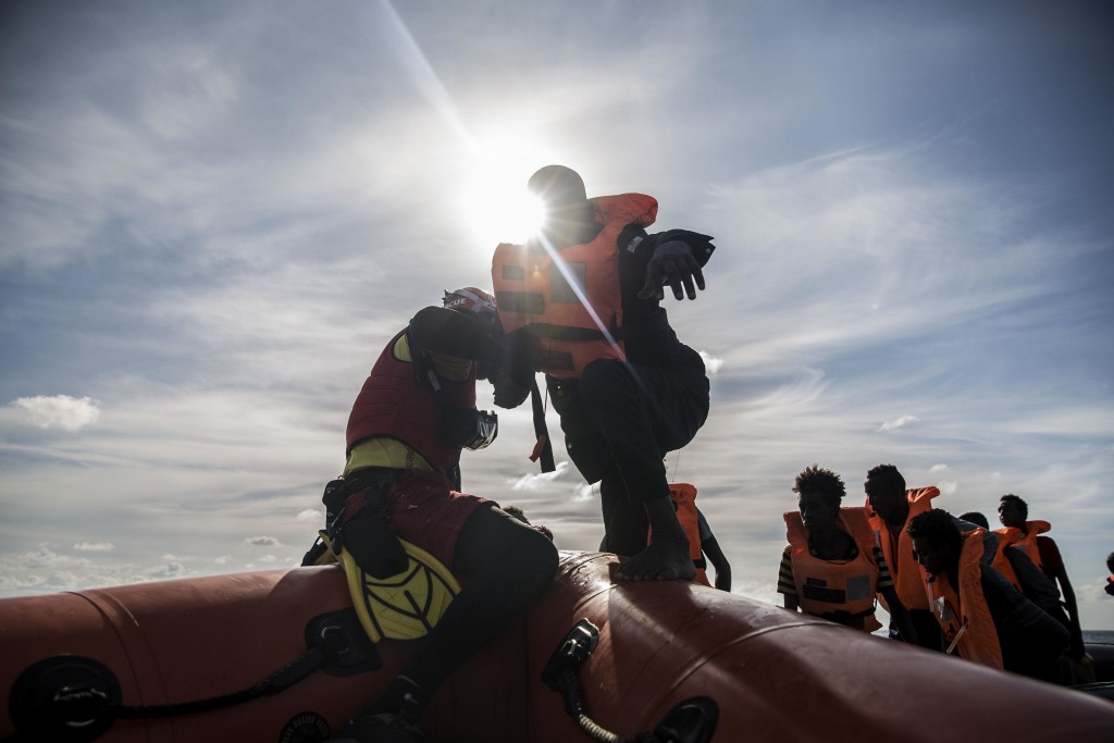 In this Friday, Dec. 21, 2018 photo, a man is helped by aid workers of Spanish NGO Proactiva Open Arms, after being rescued in the Central Mediterrane