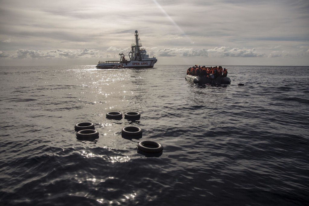 In this Friday, Dec. 21, 2018, photo, migrants sit in a rubber dinghy after Proactiva Open Arms, a Spanish NGO, spotted and rescued them in the Centra...