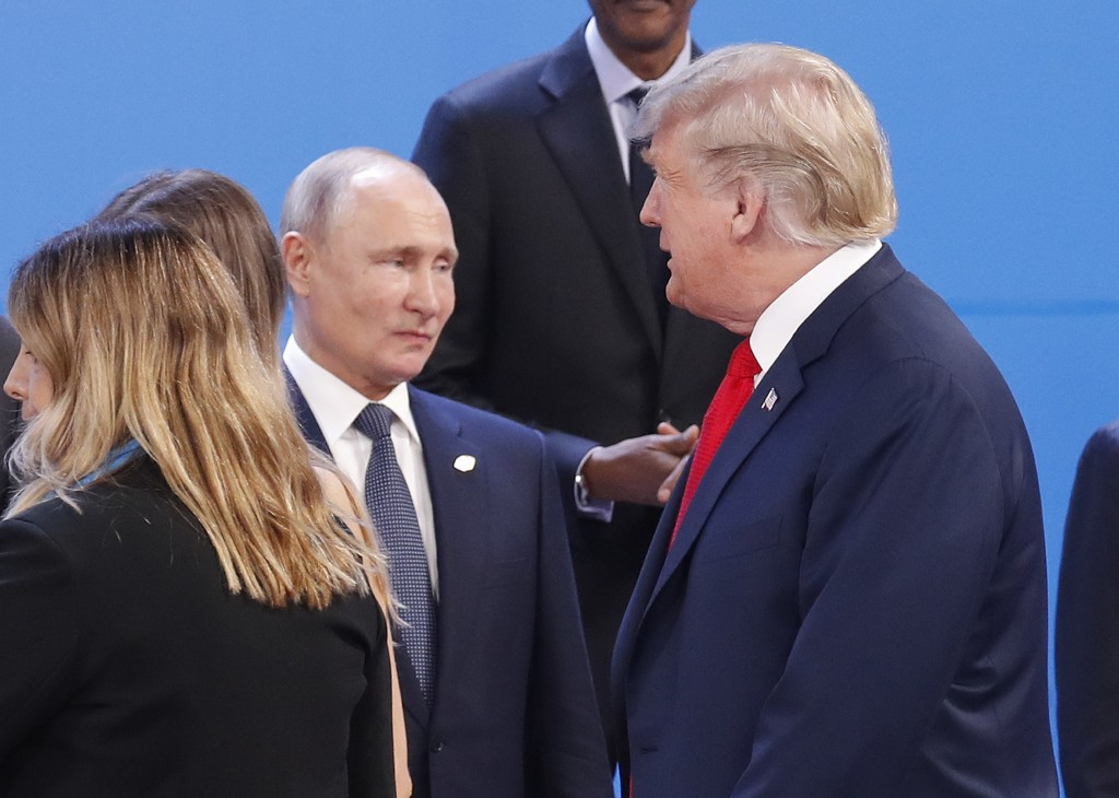 FILE - In this Nov. 30, 2018, file photo, President Donald Trump, right, walk past Russia's President Vladimir Putin, left, as they gather for the gro...