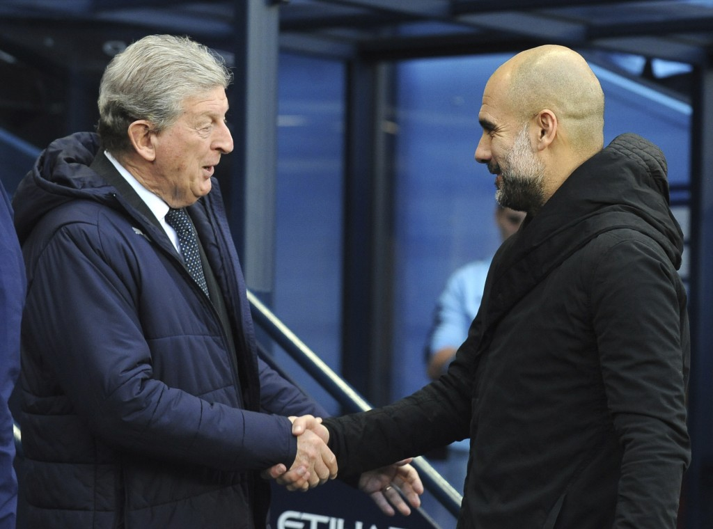 Manchester City manager Josep Guardiola, right, and Crystal Palace manager Roy Hodgson shake hands prior to the English Premier League soccer match be...