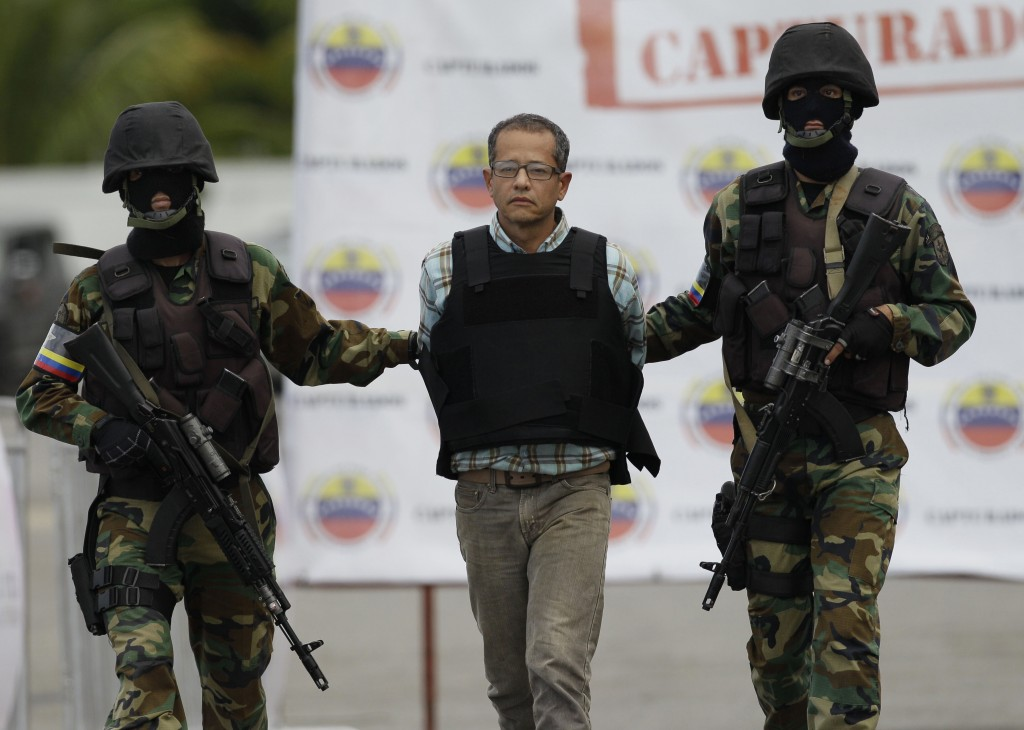 FILE- In this Nov. 14, 2012 file photo, Colombian Jorge Milton Cifuentes Villa, is escorted by National Guard officers during his deportation to Colom...