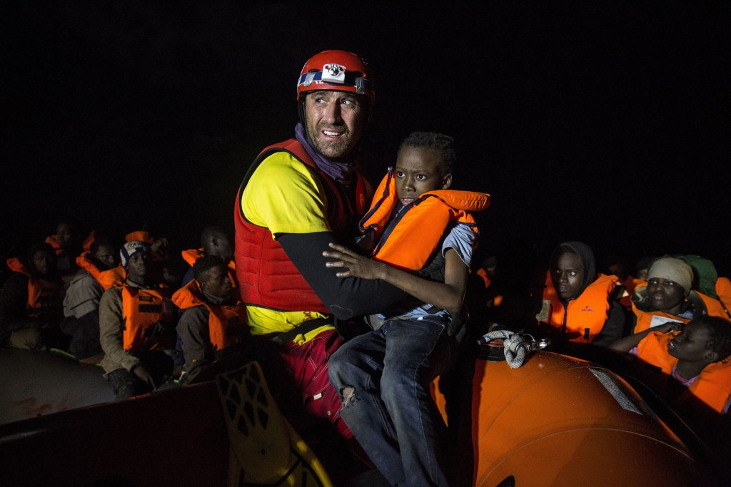 In this Friday, Dec. 21, 2018, photo, a boy is helped by an aid worker from the Spanish NGO Proactiva Open Arms, after being rescued in the Central Me...