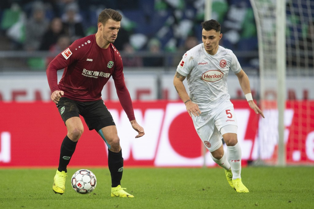 Hannover's Hendrik Weydandt, left, and Duesseldorf's Kaan Ayhan, right, challenge for the ball during the German Bundesliga soccer match between Hanno...